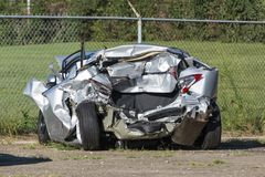Demolished Car Next to a Fence. Horizontal shot of a car demolished by a wreck Stock Image