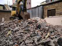 Demolished concrete and brick rubble debris. With excavator Royalty Free Stock Photography