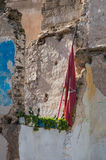 Demolished house and a moroccan flag. Ruins of an old demolished house. Structure of the walls remaining. Moroccan flag and fresh plants in the pots Royalty Free Stock Images