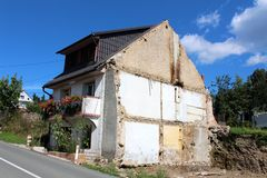Demolished part of family house waiting for rebuilding with other part untouched next to paved road with trees and houses. On cloudy blue sky background stock image
