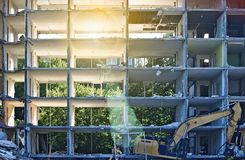 Demolished residential building with outside walls missing, sunlit with lens flare. Demolished apartment building with outside walls missing, sunlit with lens Royalty Free Stock Photo