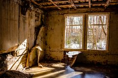 Inside an abandoned wooden structure. Sunbeams through the window on the icy floor royalty free stock images