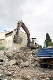 Demolishing. Cleaning ruins of building with bulldozer Royalty Free Stock Images