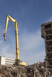 Demolition. Work on the building site of new office centre in Prague Florenc Hydraulic arm with  jaws against the blue sky. Ruins of concrete building in the royalty free stock photography