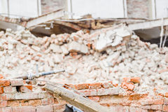 Demolition. Industry machine taking down walls of old factory building Royalty Free Stock Images