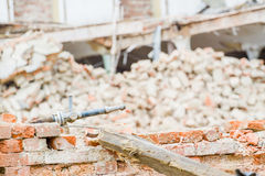 Demolition. Industry machine taking down walls of old factory building Stock Photography