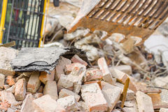 Demolition. Industry machine taking down walls of old factory building Royalty Free Stock Photo