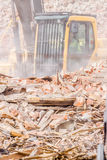 Demolition. Industry machine taking down walls of old factory building Stock Images