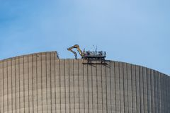 Demolition of the atomic chimney. Remote controlled excavator with shears works from above. royalty free stock image