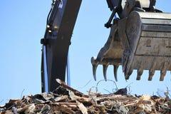 Demolition with backhoe loader. Backhoe front loader filling up and crushing large building Royalty Free Stock Photography