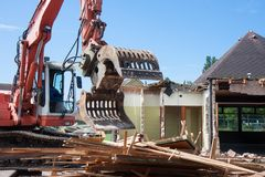 Demolition of a building with a excavator Royalty Free Stock Images