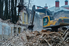 The demolition of building, excavator in work, destruction and ruins Stock Images