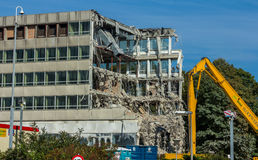 Demolition of a building by a high reach excavator Stock Photo