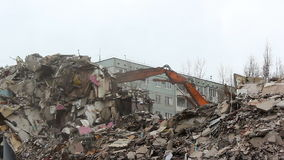 Demolition of building in urban environments with heavy machinery stock video