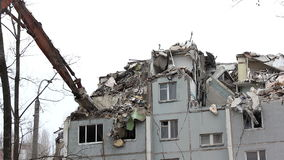 Demolition of building in urban environments with heavy machinery stock video footage
