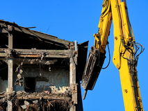 Demolition of buildings. Demolishing the building using a machine Stock Photos