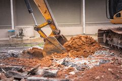 Demolition of buildings. Having to use a machine such as the backhoe to demolish can save time and save human labor Stock Image