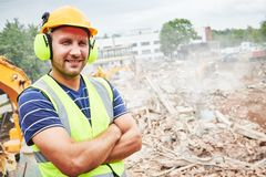 Demolition construction work. Worker at building site royalty free stock photo