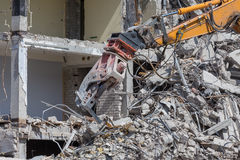 Demolition crane dismantling a building. Pieces of Metal and Stone are Crumbling from Demolished Stock Photography