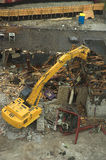 Demolition crunch. Yellow crane demolishes building Stock Images