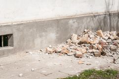 Demolition and destruction site bricks remains of building material on the ground by the house foundation base.  Stock Images