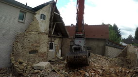 Demolition. Excavator is demolishing a house and clearing debris stock video