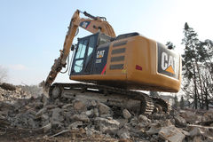 Demolition excavator destroys abandoned buildings in Milovice. Royalty Free Stock Photo