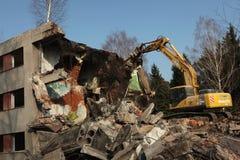 Demolition excavator destroys abandoned buildings in Milovice. Stock Image