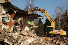 Demolition excavator destroys abandoned buildings in Milovice. Stock Images