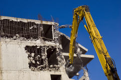 Demolition with excavators. Destruction of concrete wall of old building with excavators stock photography