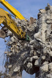Demolition with excavators. Destruction of concrete wall of old building with excavators royalty free stock photo