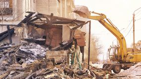 Demolition house using excavator in city. Rebuilding process. Remove equipment royalty free stock photos