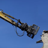 Demolition machine. Closeup view of the arm of a machine in the process of demolishing the brick wall of a building, isolated against a cloudless blue sky Stock Photography