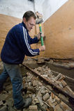 Demolition man. A builder holding up a big hammer, demolishing a room, early stage of a house improvement Royalty Free Stock Photos