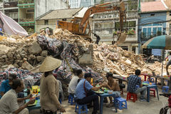 Demolition of old building in Ho Chi Minh, Vietnam. Demolition team demolishing old building in Ho Chi Minh city in District 1 in Vietnam while people eat in Royalty Free Stock Photo