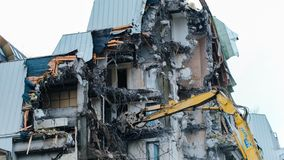 Demolition of an old building, time-lapse. Excavator destroys old building stock image