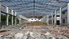 Demolition of an old factory building zooming in with an excavator working in the far end stock video footage