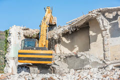 Demolition of an old house with excavator Royalty Free Stock Photos