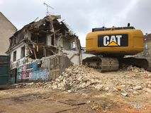 Demolition of an old house with yellow cat Excavator power shovel for building new apartments. Copenhagen, Denmark - March 14, 2018: Demolition of an old house Stock Images