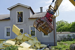 Demolition of a residential house. Removing of insulation material and a digger at the demolition of a residential house Stock Photo