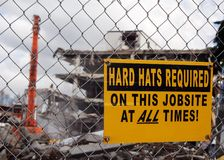 Demolition site. Hard Hats Required sign on a mesh fence of a demolition site stock photography