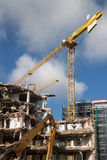 Demolition site. Demolition of building structure with heavy machines and cranes Stock Image