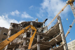 Demolition site. Demolition of building structure with heavy machines and cranes on demolish site royalty free stock image