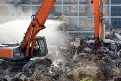 Demolition site. Of old factory building with heavy machines at work stock image