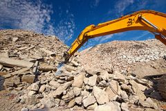 Demolition waste recycling. Construction and concrete demolition waste recycling site with crush excavator boom Stock Photos