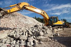 Demolition waste site. Construction and concrete demolition waste and excavator Royalty Free Stock Photography