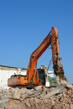 Demolition work. Demolition machine breaking old brick building into debris shot against blue sky Royalty Free Stock Images