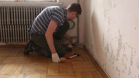Demolition work in an old apartment. Removing the baseboard stock video