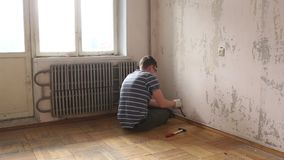 Demolition work in an old apartment. Removing the baseboard stock video footage