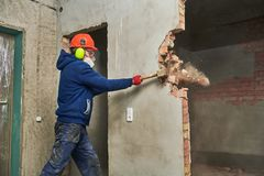 Demolition work and rearrangement. worker with sledgehammer destroying wall. Demolition work. Worker builder with sledgehammer destroying interior wall royalty free stock photography
